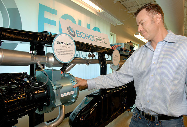 Jason Plotke, president of Echo Automotive, shows the electric motor that is part of their EchoDrive system that converts fleet vehicles into plug-in electric hybrids.