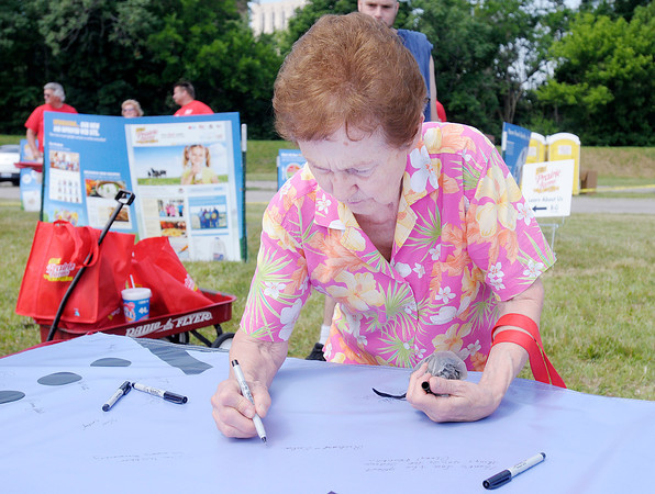 """Don Knight/The Herald Bulletin<br /> Eula Carr signs a section of the """"World's Largest Anniversary Card"""" as Prairie Farms held an event at Athletic park on Saturday to celebrate their 75th Anniversary."""