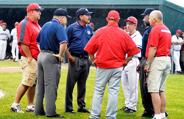 John P. Cleary | The Herald Bulletin<br /> Umpires and coaches from Wapahani and Frankton confered behind home plate as the rain continued to fall on whether to wait or postpone their 2A sectional baseball game Monday. The game will be played Tuesday afternoon at 5 p.m.