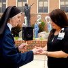 John P. Cleary | The Herald Bulletin<br /> Sister Dolores Marie Rathnow blesses the hands of Christina Welch of the St. Vincent Medical Group during the 120th Birthday celebration Monday morning at St. Vincent Anderson Regional Hospital. The blessing prayer asked for the hands to be blessed and guided as instruments of healing.