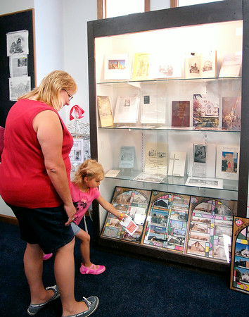 """John P. Cleary   The Herald Bulletin<br /> Madison County Historical Society's new exhibit """"Active Madison County Churches Over 100 Years Old.""""  Here Ella Brooks, 4, points out a church to her mother Karen Brooks as they look through the exhibit."""