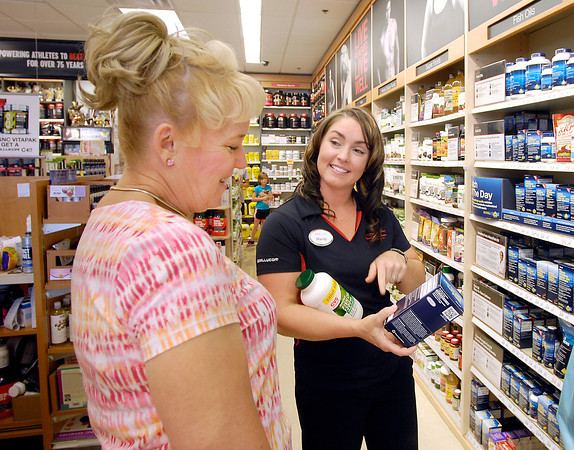 John P. Cleary   The Herald Bulletin<br /> Mandy Vermillion, right, GNC store manager, assists customer Sally Davis with product comparison  as she shops at the store at 2309 Charles Street in Anderson.