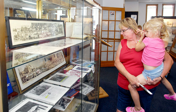 """John P. Cleary   The Herald Bulletin<br /> Madison County Historical Society's new exhibit """"Active Madison County Churches Over 100 Years Old.""""  Here Karen Brooks her daughter Ella Brooks, 4, look through the exhibit."""