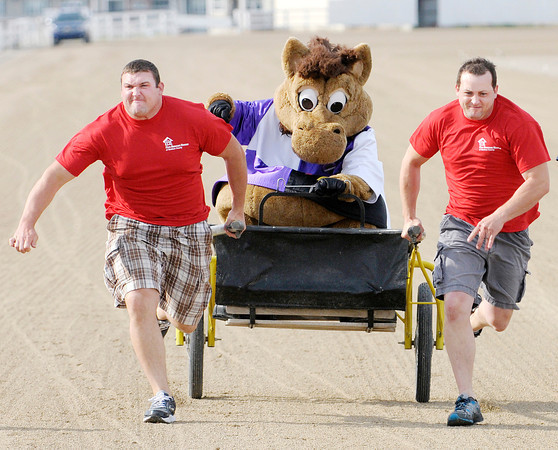 Don Knight   The Herald Bulletin<br /> Brothers and Elwood firefighters Cory, left, and Matt Boyland pull Hoosier Park mascot Hoosier Buddy in a sulky race during the Guns and Hoses event at Hoosier Park on Saturday. To view or buy this photo and other Herald Bulletin photos, visit photos.heraldbulletin.com.