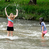 John P. Cleary | The Herald Bulletin<br /> Logan Harrison, 12, splashes up water toward her cousin Camille Ortiz, 8, while playing in the water at Falls Park in Pendleton Tuesday afternoon.<br /> Harrison, from Ohio, and Ortiz, from Texas, are in Indiana visiting their grandmother and were at the park on a family outing enjoying the day.
