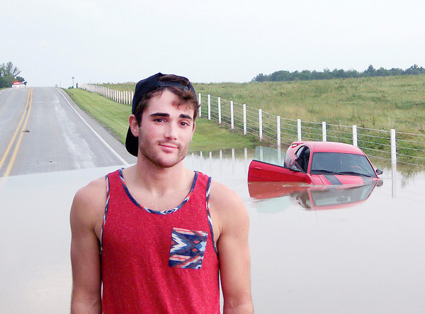 Ken de la Bastide | The Herald Bulletin<br /> Sheridan resident Kyle Jones drove his Ford Mustang into the ditch to avoid an accident with cars slowly driving through high water on Indiana 128 West of Frankton on Thursday.