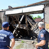 John P. Cleary | The Herald Bulletin<br /> Anderson Fire Department personnel check out the damage from a partial roof collapse of the old factory building at 1500 West 2nd Street that Anderson Transit System uses as their school bus garage.