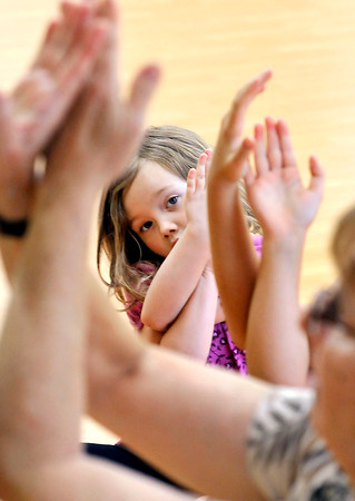 John P. Cleary   The Herald Bulletin<br /> Sailor O'Brien, 5, tries to follow yoga instructor Bianca McRae as she shows a pose that intertwines the arms during the Fun with Yoga program for children at the Anderson Public Library Tuesday.