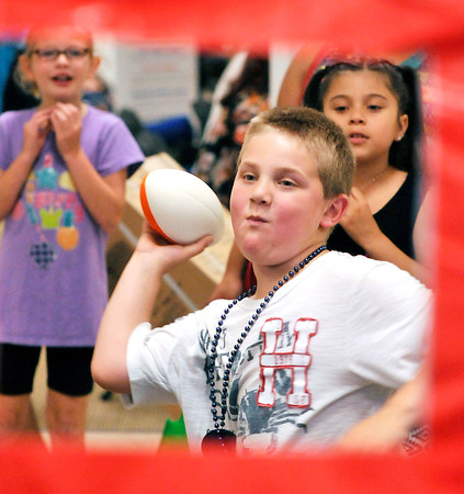 John P. Cleary   The Herald Bulletin<br /> Jaxson Marsh, 7, takes aim with the football to try and win a prize if he hits the target during the Community Safety Fair and family fun day at the Mounds mall Wednesday afternoon.
