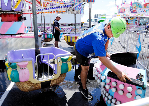 """Don Knight   The Herald Bulletin<br /> Heinrich Habig cleans one of the rides at Hoosier Park's """"Hoosierfest Carnival"""" as workers from North American Midway Entertainment set up the rides, games and concessions on Wednesday. The carnival opens Friday at 5 p.m. and runs through Monday from 11 a.m. to 11 p.m. Unlimited ride passes are $25."""