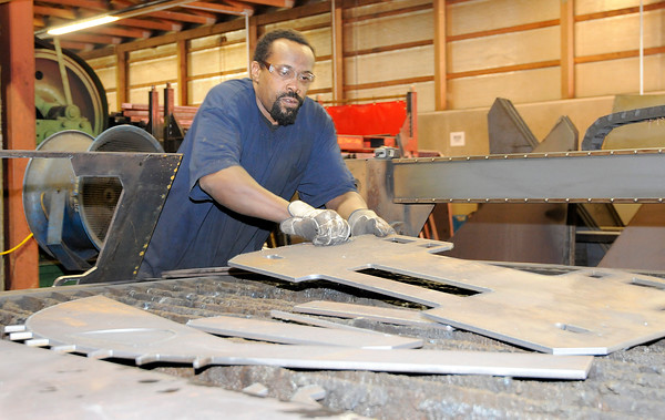 Don Knight   The Herald Bulletin<br /> Antoine Turner removes a piece of cut steal from a plasma cutting table at Steel-Mart in Alexandria on Thursday. When Turner got out of prison four years ago he decided to turn his life around but not many companies will hire someone with a felony record but Madison County's Steel-Mart him a chance to start over.