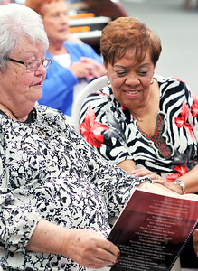 John P. Cleary |  The Herald Bulletin Bonnie Drayer and Teresa Granger, both from Noblesville, look over a music book to select an other song to play when their turn comes back around during the weekly Friends playing for Friends gathering at Lambert's Music Center.