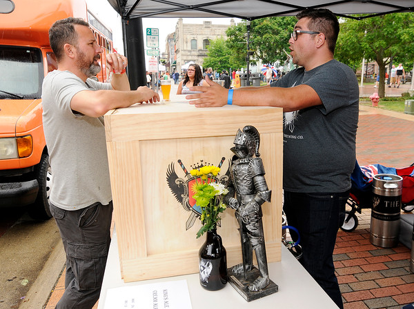 Don Knight   The Herald Bulletin<br /> Shane Kelly, left, talks to Jarrod Case about the Guardian Brewing Company from Muncie during Anderson On Tap at the Dickmann Town Center park on Saturday. Guardian Brewing opened last November and brought six different beers to Anderson On Tap.