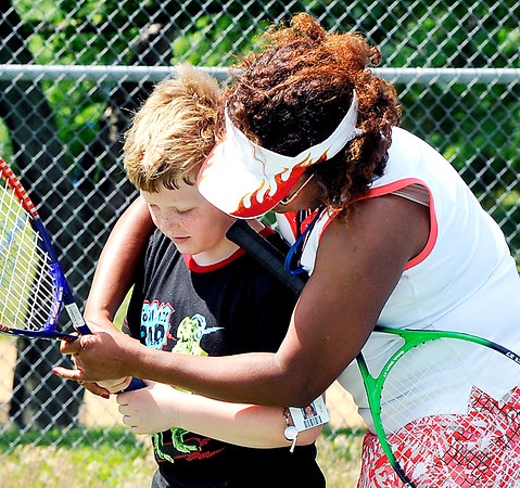 John P. Cleary | The Herald Bulletin<br /> Dr. Treva Bostic shows this youth the proper grip on the tennis racket during the Anderson Parks Department summer youth program outing at Pulaski Park Thursday.