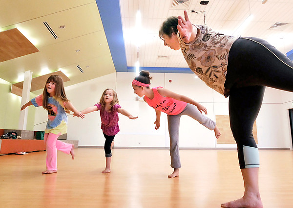 John P. Cleary | The Herald Bulletin<br /> The Fun with Yoga program for children at the Anderson Public Library Tuesday was led by yoga instructor Bianca McRae, right, introducing kids to yoga and it's different positions.