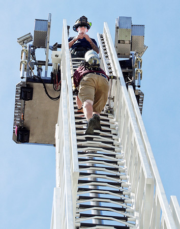 Mark Maynard   For The Herald Bulletin<br /> As Ryan Souder of the Elwood Fire Department awaits on the platform, Alexandria Fire Department recruit Joel Nichols nears the top of EFD's 100 foot snorkle.