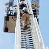 Mark Maynard | For The Herald Bulletin<br /> As Ryan Souder of the Elwood Fire Department awaits on the platform, Alexandria Fire Department recruit Joel Nichols nears the top of EFD's 100 foot snorkle.