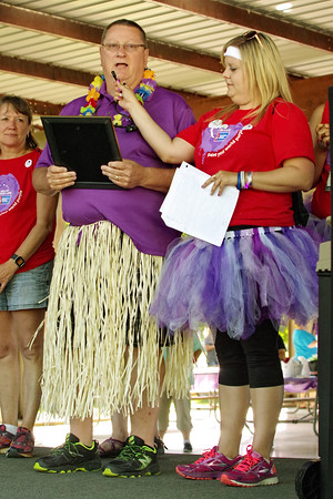 """As Relay for Life Chairperson Brittany Williams holds the microphone, Alexandria Mayor and member of the luau-themed walking team """"Pay It Forward"""" Ron Richardson reads a proclamation delcaring June 17, 2016 """"Relay for Life Cancer Awareness Day"""" in the city."""