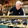 John P. Cleary | The Herald Bulletin<br /> Steve Rubenstein of Allan's Jewelry & Loan arranges the firearms display case<br /> in their store.