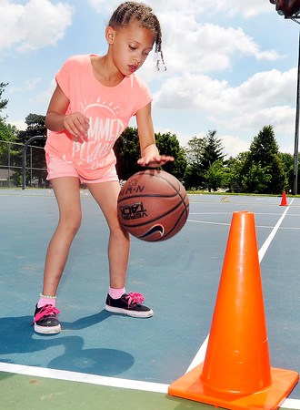 John P. Cleary | The Herald Bulletin<br /> Ameira Thompkins, 7, practices her dribble as she goes through basketball basic skills at the Anderson Parks Department summer youth program outing at Pulaski Park Thursday.