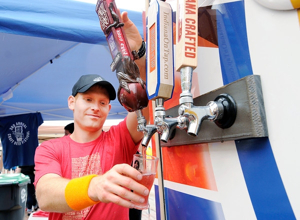 Don Knight   The Herald Bulletin<br /> Steve Williams with Indiana On Tap pours a sample of Gnarley Grove Legendary Hard Cider during the Anderson On Tap at the Dickmann Town Center park on Saturday.