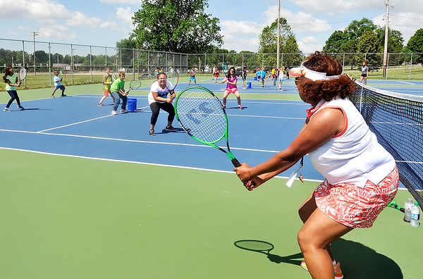 John P. Cleary | The Herald Bulletin<br /> Dr. Treva Bostic shows kids the proper setup for tennis as she teaches them the fundamentals of the game during the Anderson Parks Department summer youth program outing at Pulaski Park Thursday. The Parks Department and Anderson Community Schools teamed up to help expand the summer program to more youth in the community.<br /> <br /> <br /> Kids enjoying summer camp with outing to Pulaski Park.