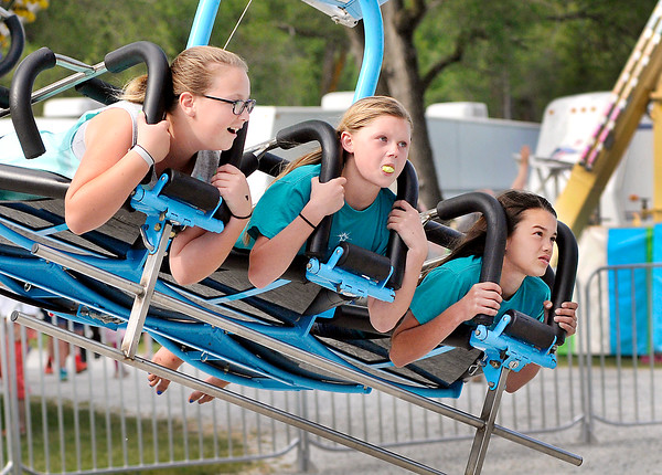John P. Cleary   The Herald Bulletin<br /> Ileah Clark, center,12, tries to blow a bubble while riding the Hang Glider with her friends Avery Mollenkopf , 12, and Alivia Swisher, 11,  Tuesday evening at the opening night of the Lions Club June Jamboree at Falls Park in Pendleton.<br /> The fair runs through Saturday.
