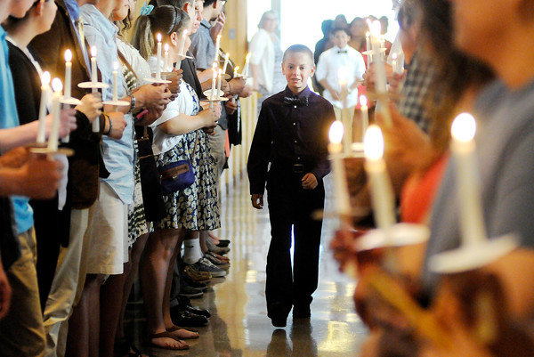 Don Knight | The Herald Bulletin<br /> A 6th grader walks past St. Ambrose alumni as the school holds its last 6th grade graduation before consolidation next year with St. Mary's.