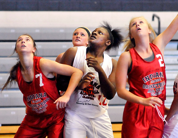 John P. Cleary   The Herald Bulletin<br /> Anderson's Kenigia Hamilton, center, fights for position to get a rebound during one of the Girls Indiana Class Basketball All-Star Classic games featuring juniors.