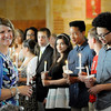 Don Knight | The Herald Bulletin<br /> St. Ambrose alumni hold candles as they wait for the procession of graduating sixth graders to start during the school's last graduation before consolidation next year.