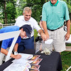 John P. Cleary |  The Herald Bulletin<br /> Luke Hammons signs a get well card for John Andretti as teammates Pete Smith and Phil Isenberger make a donation to the CheckIt4Andretti Fund on the seventh hole of the St. John's Children's Clinic Classic Tuesday.