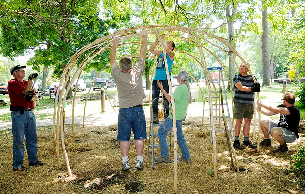 Don Knight   For The Herald Bulletin<br /> Volunteers bend a branch into place as Jessica Diemer-Eaton from the Woodland Indian Education Program secures it as the group builds a Wigwam next to the Nature Center at Mounds State Park. From left are Jerry Byard, Vance Bell, Jessica Diemer-Eaton, Kate Young Bell, Alan Simpson and Connor MacRae. The wigwam replaces an earlier one built by Diemer-Eaton during the Andersontown Powwow and moved to Mounds. The build will continue until about 4 p.m. today and anyone interested is welcome to volunteer.