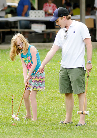Don Knight   For The Herald Bulletin<br /> Dr. Drew Gleitsmann gives Alexandra Perry, 9, some instruction in how to play croquet during the Picnic in the Park hosted by the Alexandria Monroe Chamber of Commerce and the Madison County Community Health Center in Alexandria on Thursday.