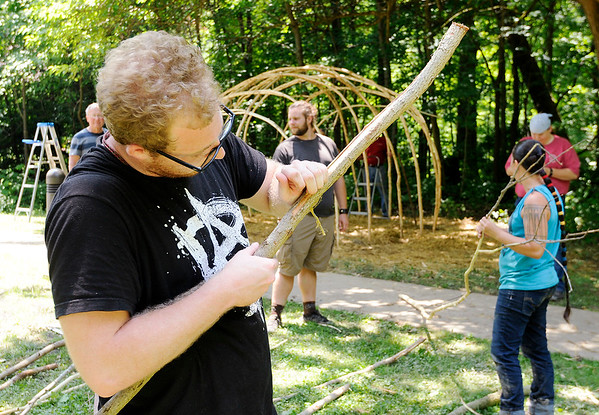 Don Knight | For The Herald Bulletin<br /> Connor MacRae strips bark from a willow branch so it can be used to build a wigwam at Mounds State Park. Removing the bark keeps insects away that would otherwise burrow under the bark and damage the wood.