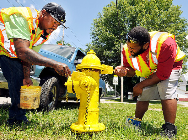 John P. Cleary    The Herald Bulletin<br /> Oscar Perry and Terrance Raymore, of the Anderson City Water Department, paint the fire hydrant in the 1600 block of Indiana Ave. Monday afternoon. <br /> Cleaning then painting hydrants is part of their summer employment responsibility with the city.