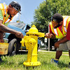John P. Cleary |  The Herald Bulletin<br /> Oscar Perry and Terrance Raymore, of the Anderson City Water Department, paint the fire hydrant in the 1600 block of Indiana Ave. Monday afternoon. <br /> Cleaning then painting hydrants is part of their summer employment responsibility with the city.