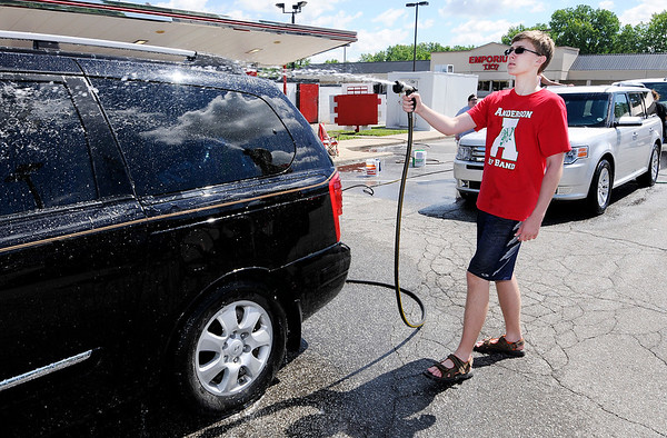 Don Knight | The Herald Bulletin<br /> Logan Hamilton, 15, rinses a minivan at Rally's on Saturday as the Anderson Marching Highlanders held a car wash to raise funds for their summer marching season. The band also washed cars at the Chesterfield-Union Township Fire Department, Firestation 8 on 53rd Street and Oak Motors. The band's first competition will be July 15th at Centerville High School.