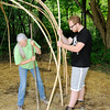 Don Knight | For The Herald Bulletin<br /> Connor MacRae holds a willow branch as Kate Young Bell tamps down soil around it to hold it in place as volunteers build a Wigwam at Mounds State Park.
