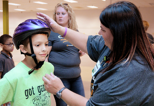 Don Knight   For The Herald Bulletin<br /> Erin Mills with Community Hospital checks the fit of a bicycle helmet on Bradley Hodges, 10, during the Community Safety Fair at the Mounds Mall on Tuesday. Kids got a bicycle safety lesson from the Spoke and Wheel bicycle club before getting a free helmet. The event at the mall brought together  local nonprofits and government agencies to give families information, free stuff, food and games.