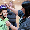 Don Knight | For The Herald Bulletin<br /> Erin Mills with Community Hospital checks the fit of a bicycle helmet on Bradley Hodges, 10, during the Community Safety Fair at the Mounds Mall on Tuesday. Kids got a bicycle safety lesson from the Spoke and Wheel bicycle club before getting a free helmet. The event at the mall brought together  local nonprofits and government agencies to give families information, free stuff, food and games.