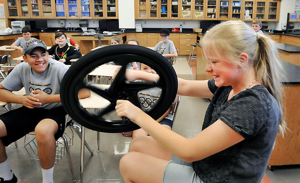 John P. Cleary |  The Herald Bulletin<br /> Ada Erny, 11, giggles as she rotates the spinning wheel to demonstrate the physical principals of inertia and torque during the Anderson Science Camp this  past week at Anderson High School.