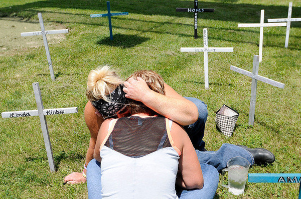 Don Knight | The Herald Bulletin<br /> Kelli Lane hugs Mary Randol before writing the name of Randol's son Dustin Billings onto a cross during the Madison County Making a Stand Against Heroin Benefit Ride on Saturday.