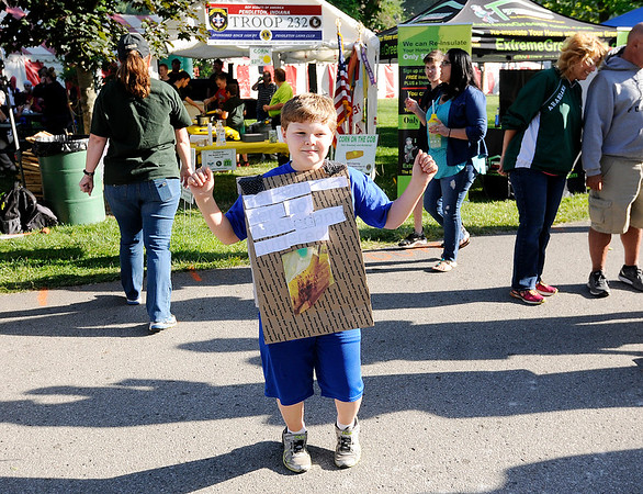 Don Knight | For The Herald Bulletin<br /> Morrison Hurt, 12, wears a sandwich board as he advertises roasted corn on the cob being being sold by Boy Scout Troop 232 during the June Jamboree in Pendleton. The festival runs through Saturday at Falls Park.