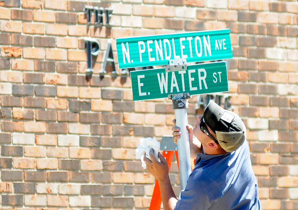 Don Knight   For The Herald Bulletin<br /> Hunter Barger with the town of Pendleton wipes down the street signs at the intersection of Pendleton Avenue and Water Street after installing new signs on Tuesday.