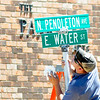 Don Knight | For The Herald Bulletin<br /> Hunter Barger with the town of Pendleton wipes down the street signs at the intersection of Pendleton Avenue and Water Street after installing new signs on Tuesday.