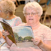 "Don Knight | The Herald Bulletin<br /> Marilyn King looks at a reproduction copy of ""Small Town, USA"" she purchased during a celebration marking the 75th anniversary of Alexandria being featured in the publication during World War II."