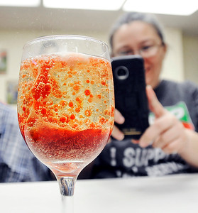 John P. Cleary | The Herald Bulletin  Iris Jensen takes a photo of the reaction of dropping an Alks Seltzer tablet into a glass of oil, water, and food coloring to create a 'Wine glass lave lamp' during the Alexandria Public Library's STEM night for adults this past week.