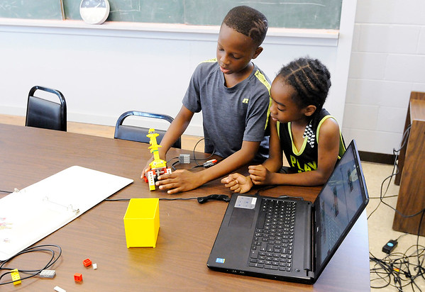 Don Knight | The Herald Bulletin<br /> From left, Jaiveon Wells and Xavier Woods build and program a roaring lion robot during Summer Camp at the Anderson Township Trustee Youth Center.