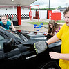 Don Knight | The Herald Bulletin<br /> From left, Lexi Mullins, Stella Parks and Garrett Dunaway wash an SUV during the Marching Highlanders car wash on Saturday. The band is raising money for their summer marching season that will culminate on August 4th at State Fair Band Day.