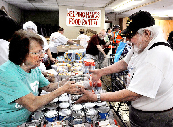 John P. Cleary | The Herald Bulletin<br /> The St. John's Lutheran Church Helping Hands Food Pantry distributed its 5 millionth pound of food Monday evening. Here volunteer Betty Jo Hughes assists Terry Bookout with some of his selections as he goes through the pantry line Monday evening.